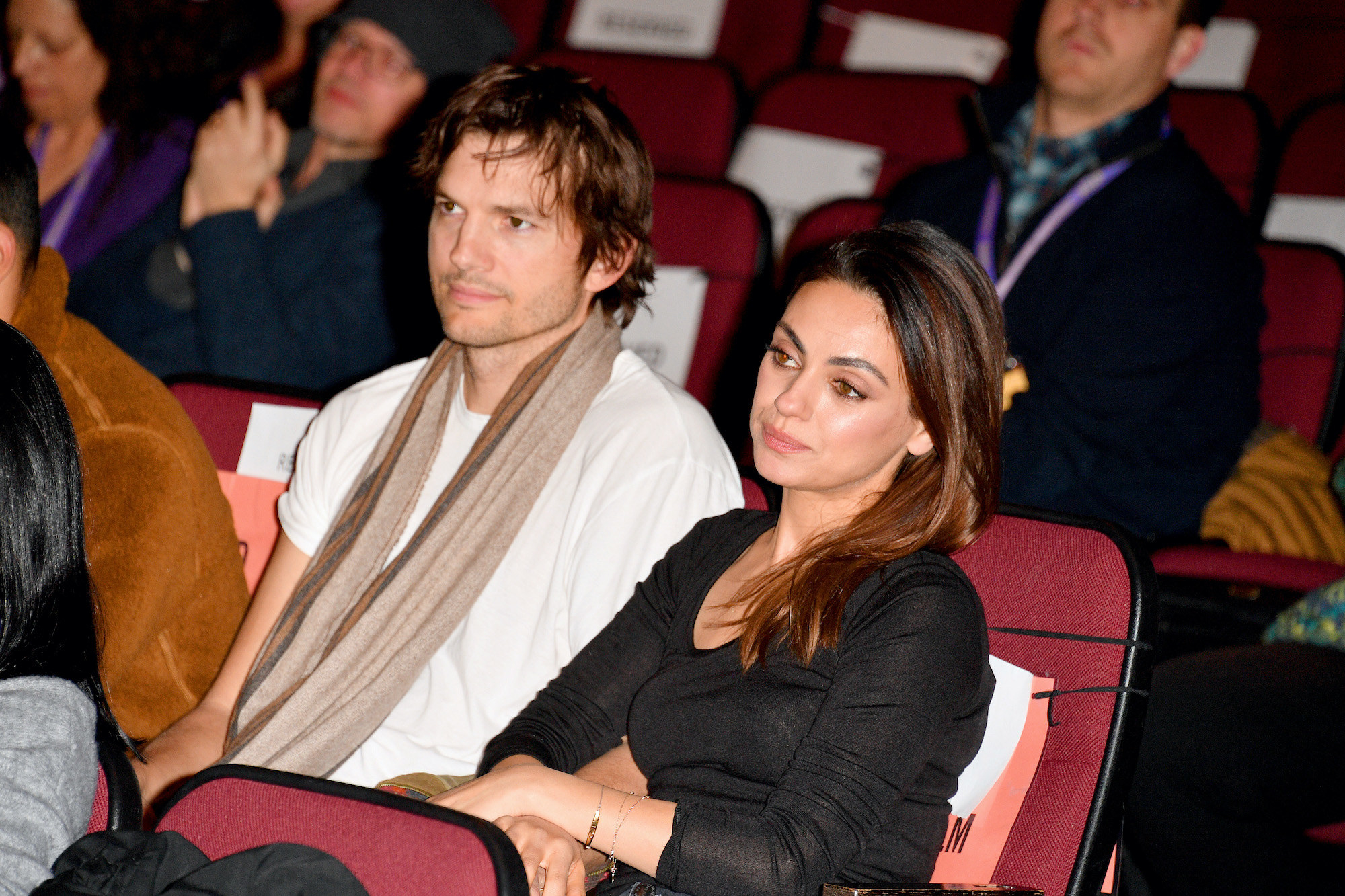 Ashton Kutcher, in a t-shirt and a scarf, and Mila Kunis, in a long-sleeved T-shirt, sitting next to each other during at the 2020 Sundance Film Festival