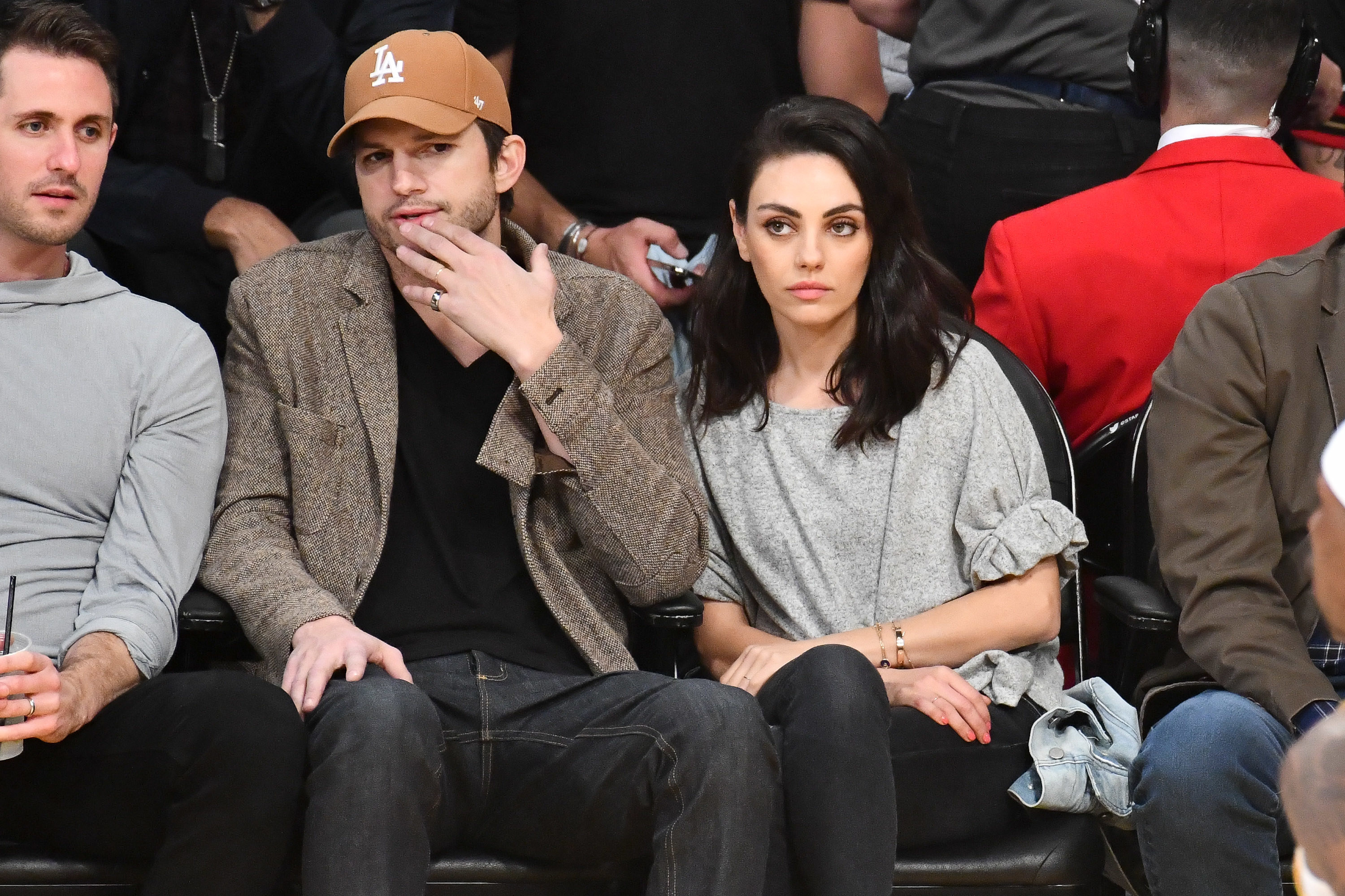 Ashton Kutcher, wearing a Los Angeles Dodgers baseball cap, jacket, v-neck, and jeans sits next to Mila Kunis, wearing a casual shirt and pants, while watching a Los Angeles Lakers Game