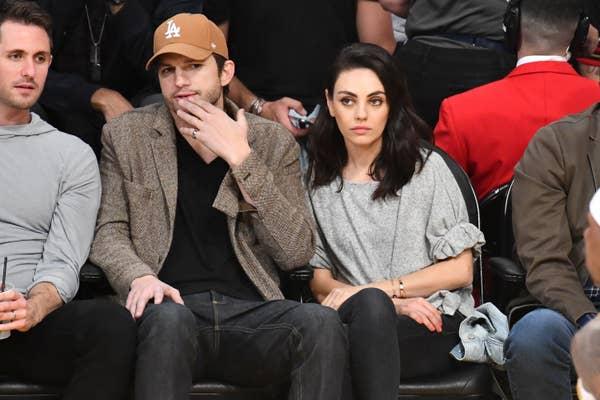 Ashton Kutcher, mengenakan topi baseball Los Angeles Dodgers coklat, jaket beige, v-neck hitam, dan jeans duduk di sebelah Mila Kunis, mengenakan kemeja abu-abu dan celana hitam, saat menonton pertandingan Los Angeles Lakers