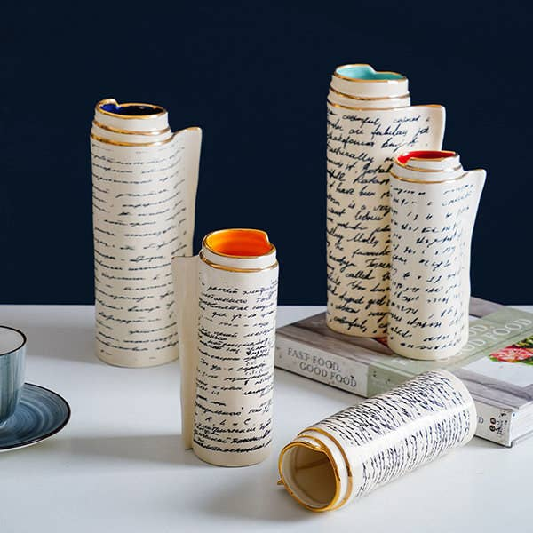 five of the ceramic vases made to look like rolled-up sheets of paper with notes scrawled on them