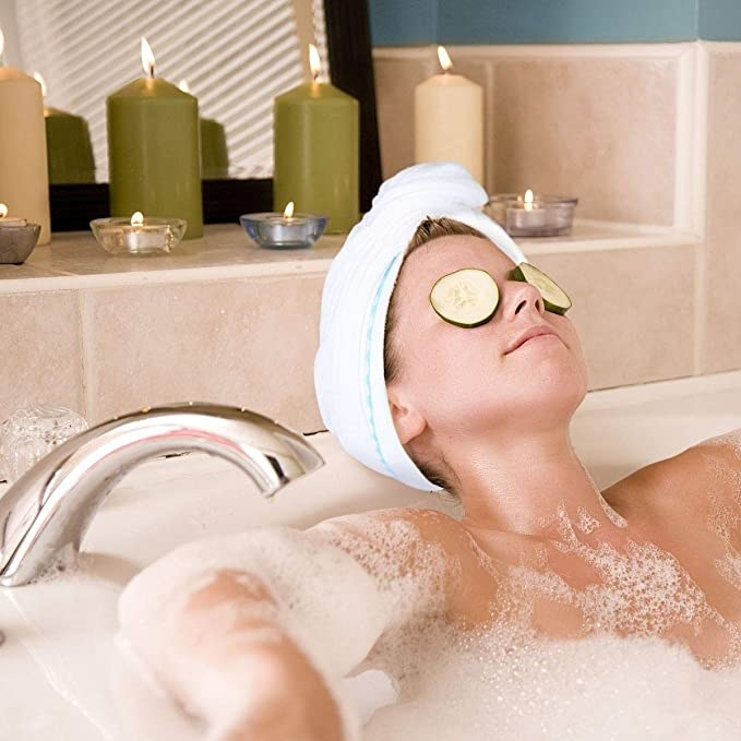 Woman lying in a tub with the towel wrapped around her hair.
