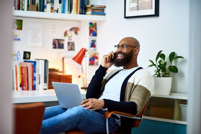 Man sitting and talking on the phone while on his laptop