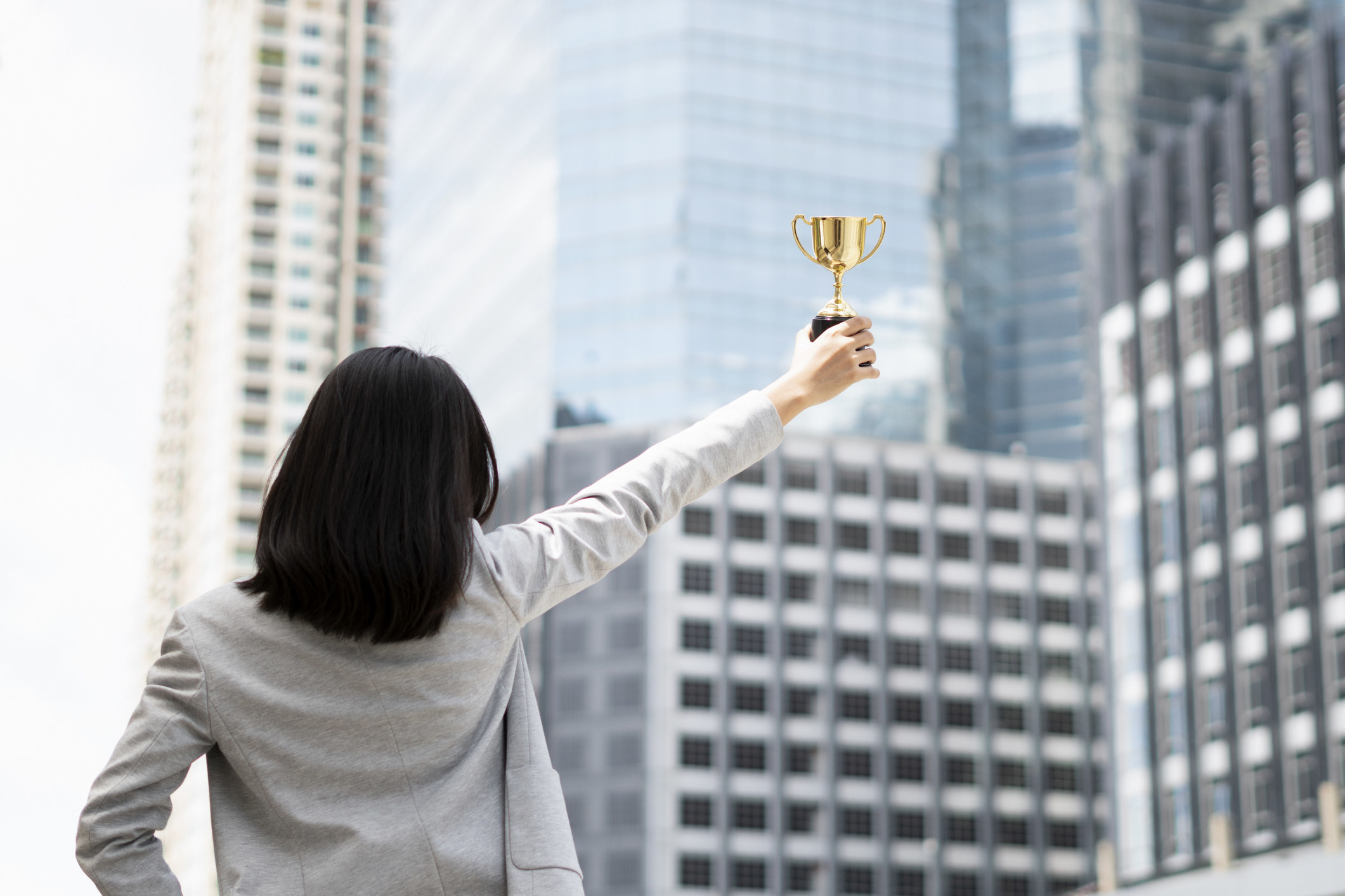 A woman holding up a small trophy as she looks at skyscrapers