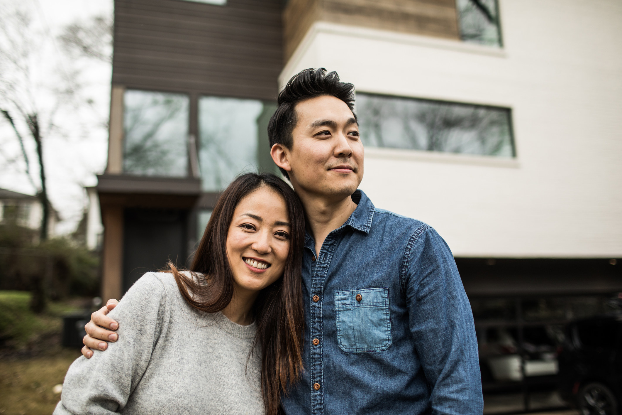 A young woman and man embracing and standing in front of a house