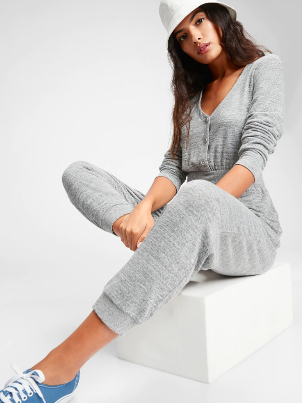 A person sitting on a block wearing a jumpsuit with a banded waist and buttons on the bodice