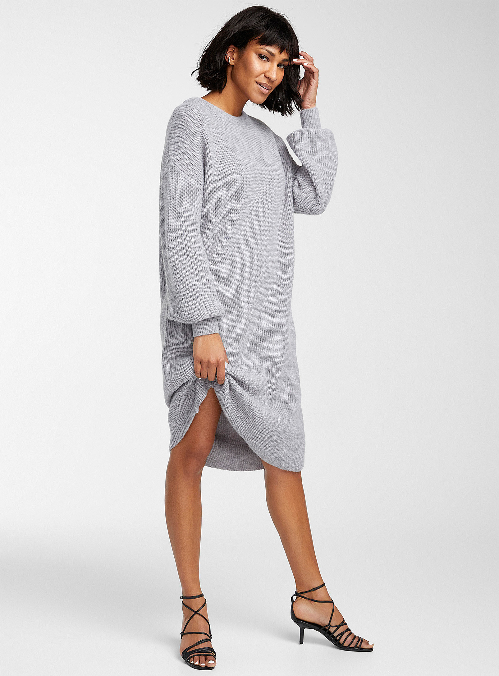 A person wearing a long-sleeved knit dress with heels