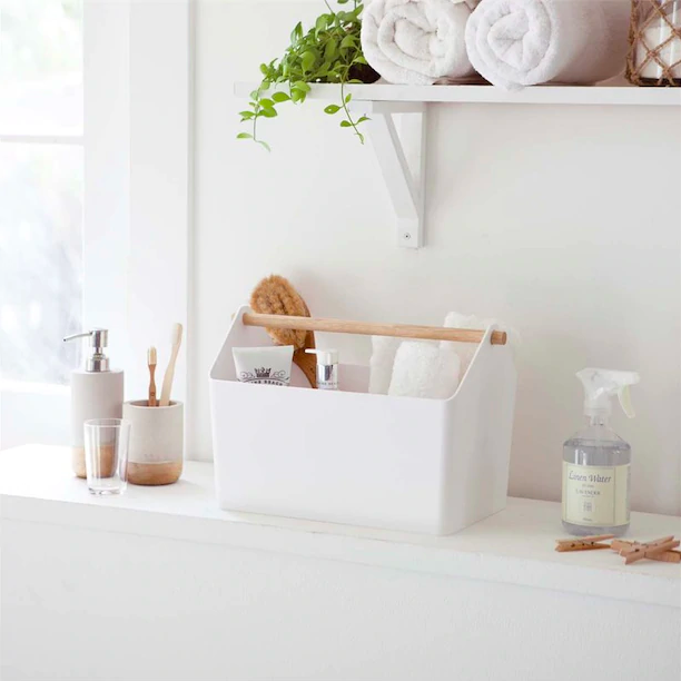 A rectangular basket with wooden handle that's filled with towels soap, and other bathroom items