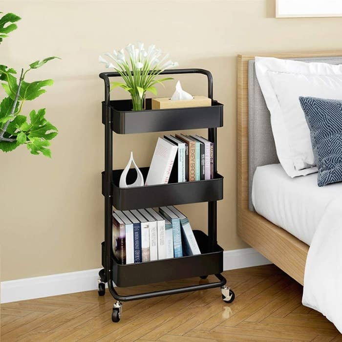 A rolling cart with three deep shelves next to a bed, each basket has a row of books in it