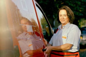 A female postal work in the United Kingdom standing next to her truck