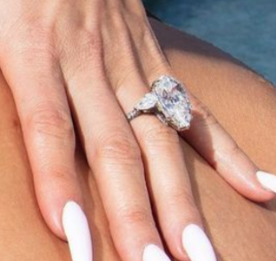 The ring has a pear-shaped diamond flanked by two smaller diamonds