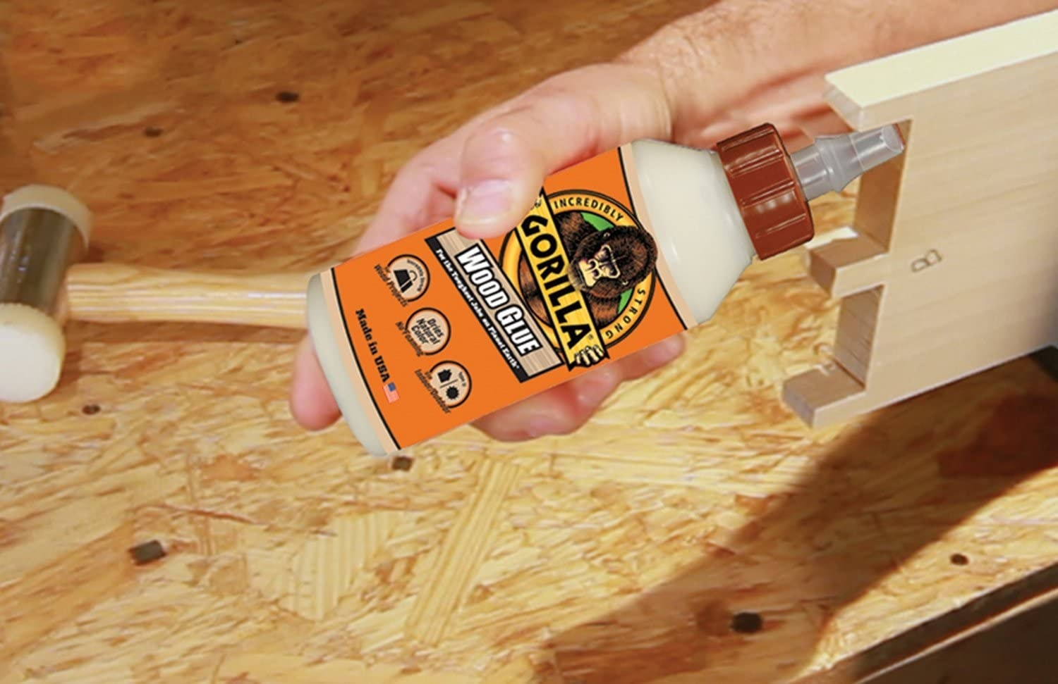 A person applying glue to a piece of wood