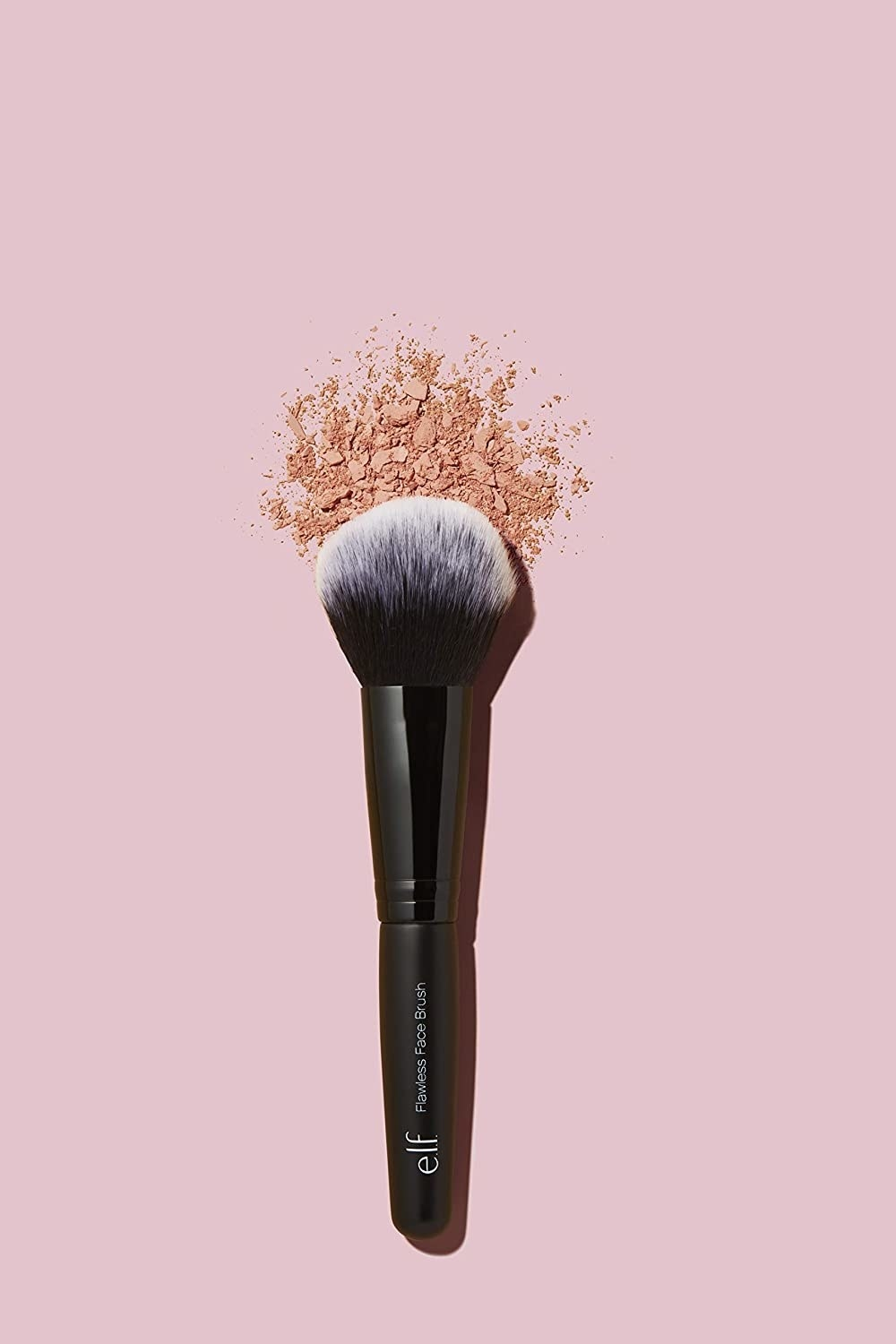 A dense fluffy makeup brush next to a swatch of loose powder
