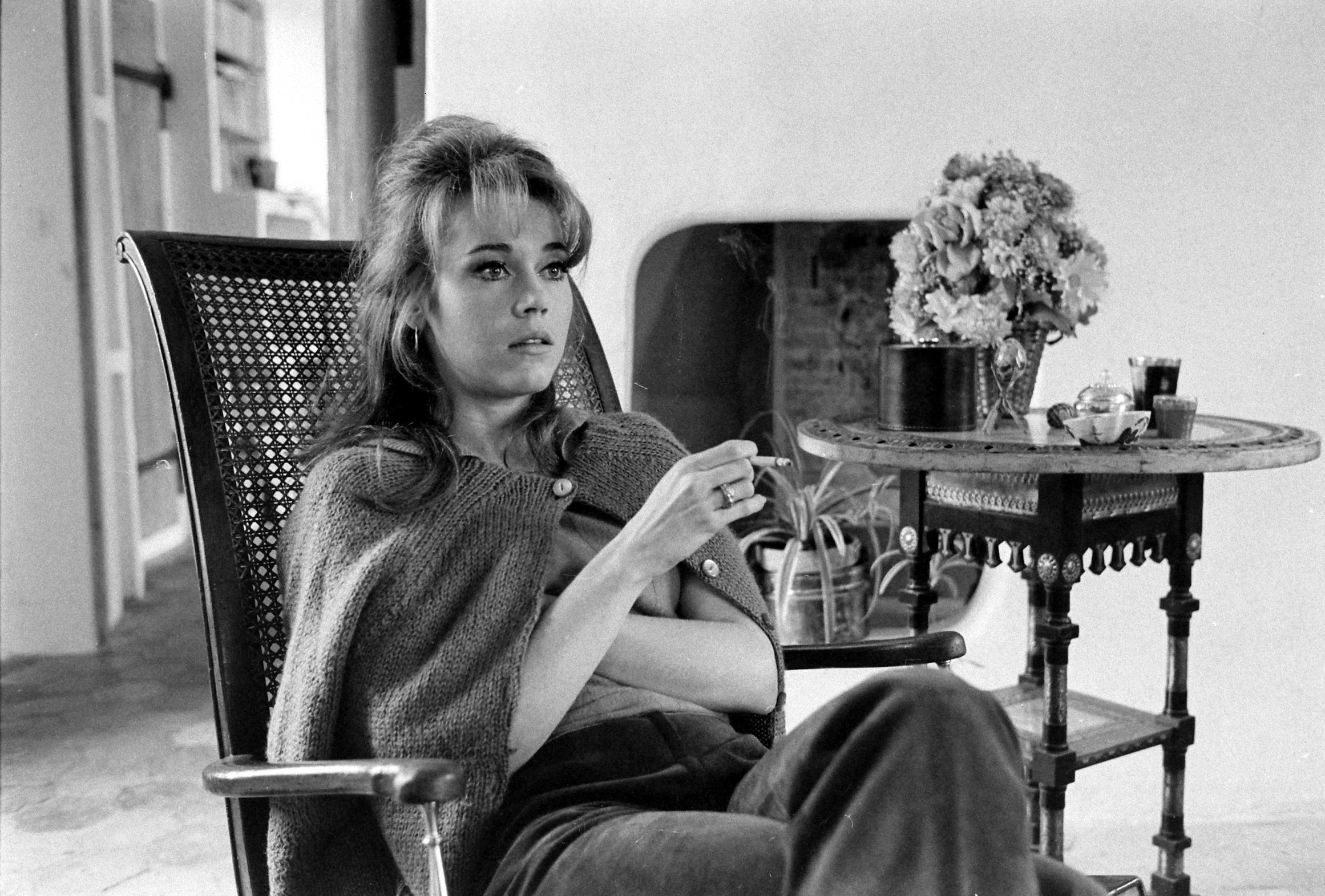 Young Jane sitting in a chair and holding a cigarette