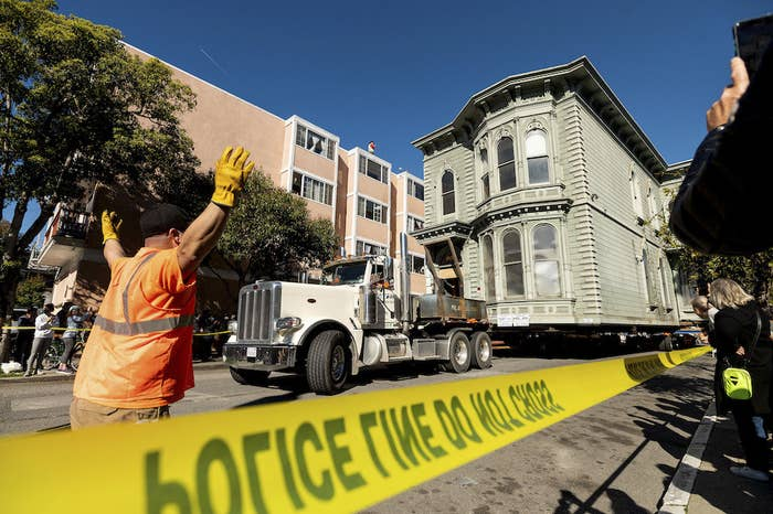Front view of truck pulling the house along the street, with police line sealing off the area