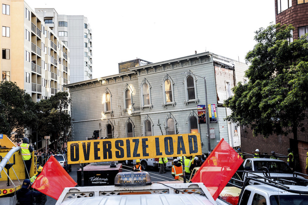"""Sign reading """"Oversize Load"""" in front of house on wheels"""