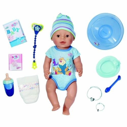 Baby Born doll with a pacifier wearing a onesie, with a potty, pacifier, food bowl and toys surrounding it