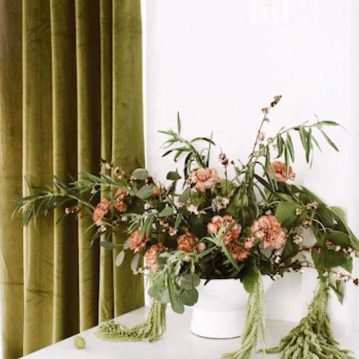 Moss green curtain behind bouquet