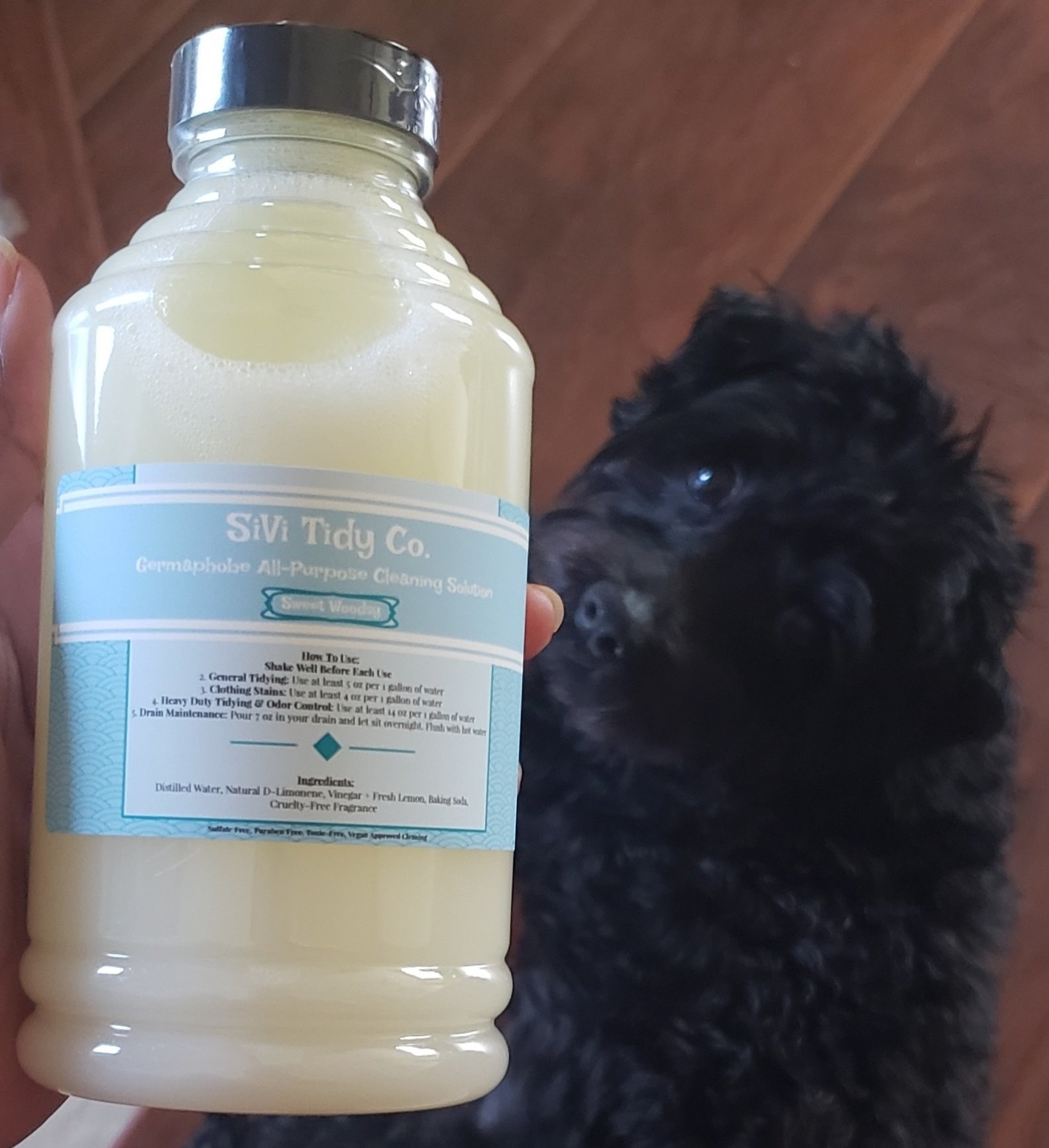 the bottle of sivi tidy co. cleaning solution next to a black dog