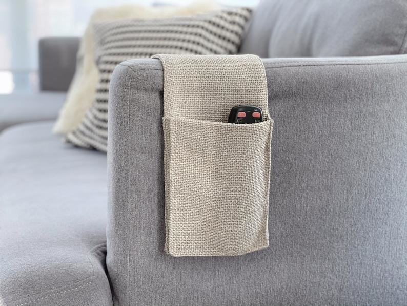 the tan caddy resting on a sofa arm and holding a remote in one large pocket