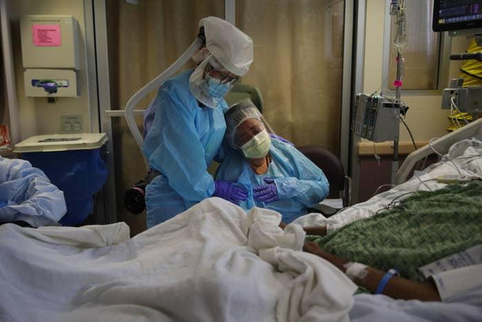 A nurse, wearing a face shield and other protective gear, holds a woman, also wearing PPE, who cries with a gloved hand pressed to her chest while sitting beside a hospital bed