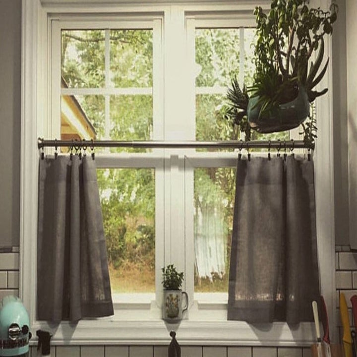 Two short curtains covering the bottom half of a window above the kitchen sink