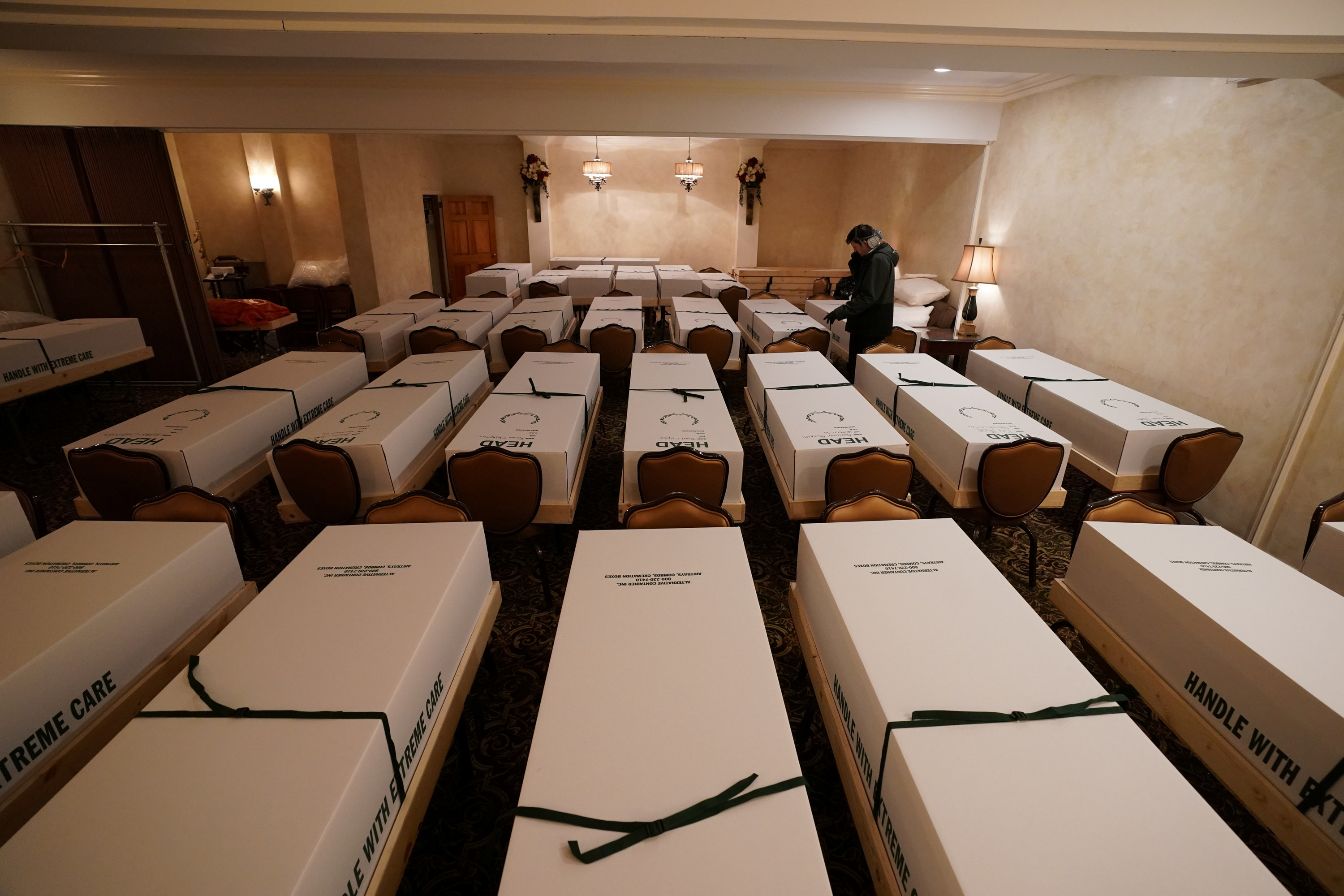 A camera overlooks multiple rows of caskets that rest on chairs inside a funeral home as one man stands in the middle of them