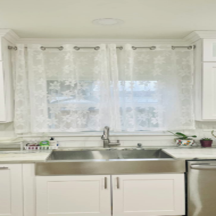 White and stainless steel kitchen with sheer lace curtains in front of kitchen window, hung with a matching stainless steel bar