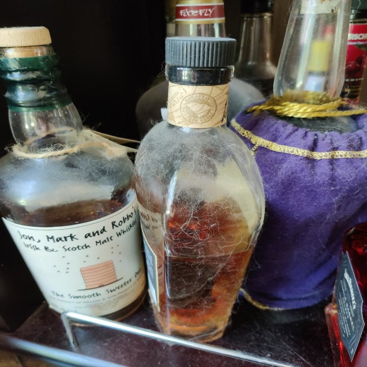 Reviewer image of grime and pet hair on liquor bottles