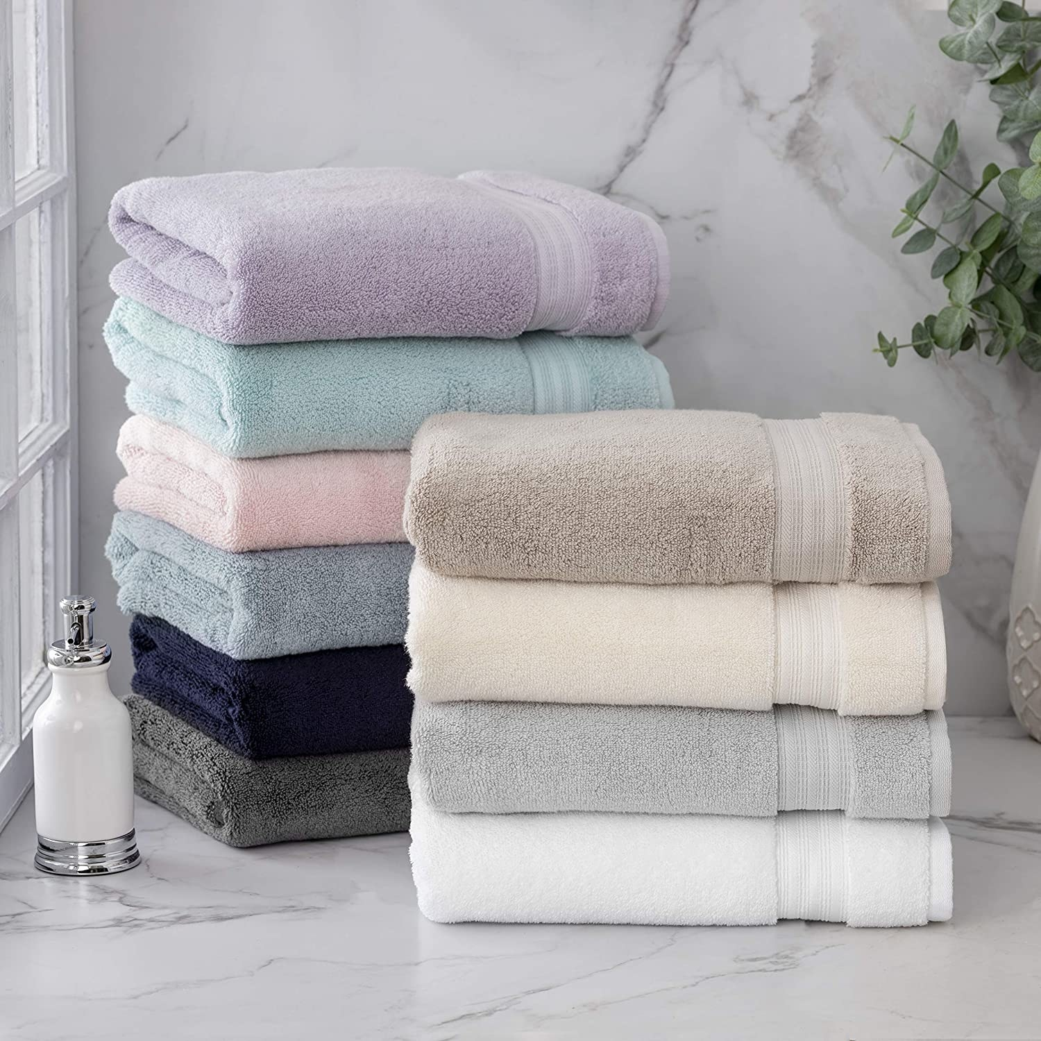 A stack of neatly folded bamboo bath towels on a marble vanity