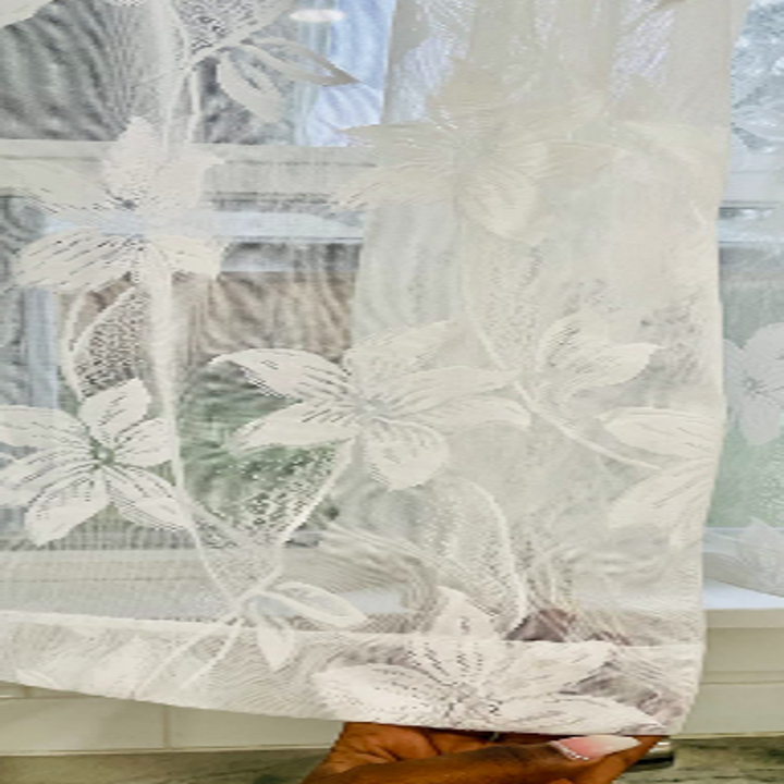 Reviewer holding curtain showing closeup of floral pattern