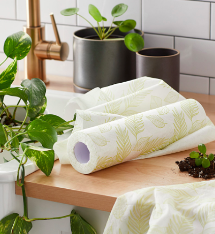 A roll of the reusable cloths on a wooden countertop next to healthy plants