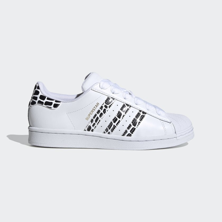 A pair of white sneakers with black animal print