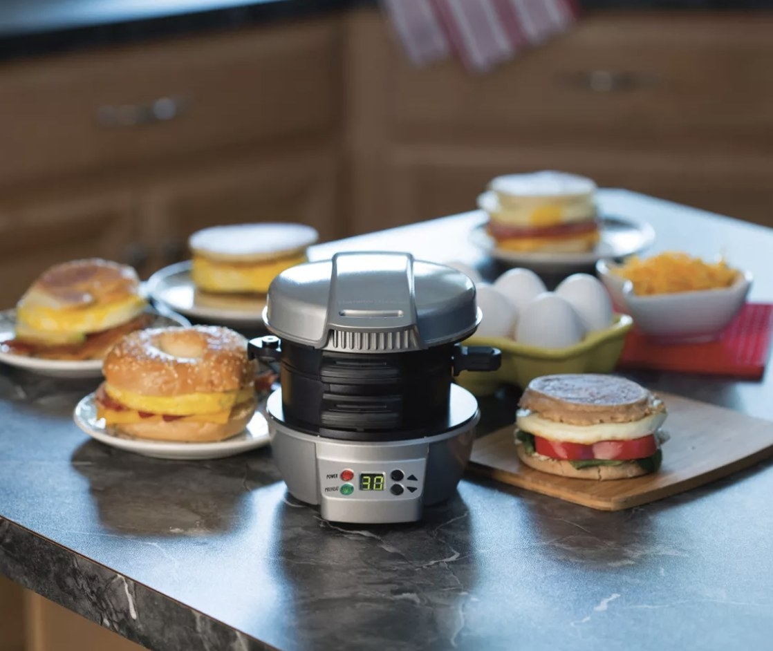The sandwich maker next to several breakfast sandwiches