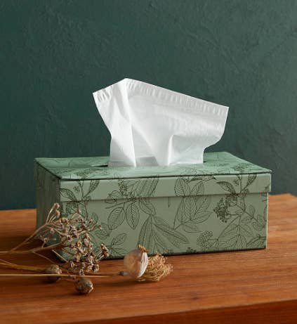 A printed tissue box cover with some tissues sticking out