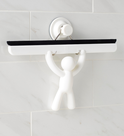 A squeegee hung on a tile wall with a handle shaped like a tiny person