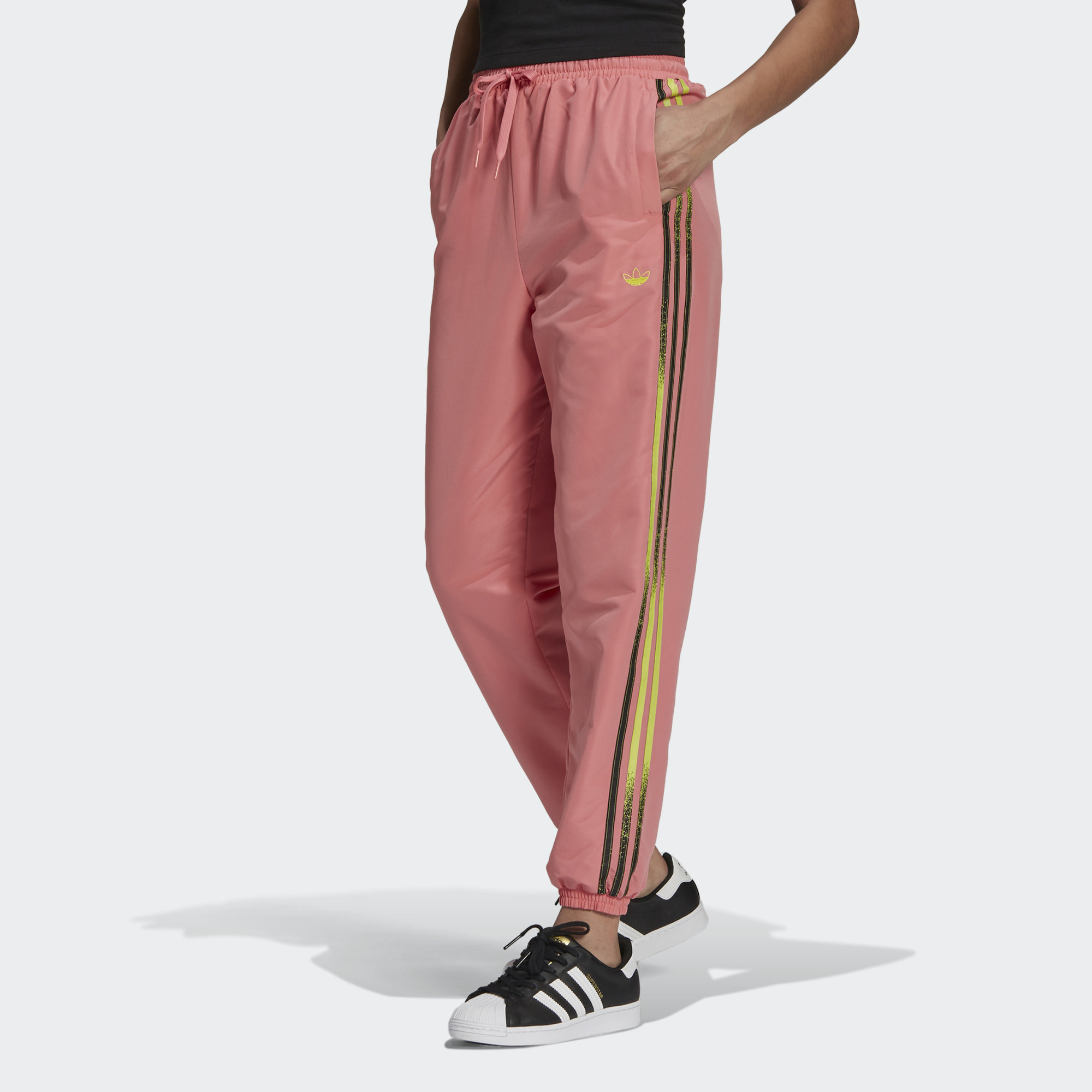Model wearing pink workout pants with gold stripe