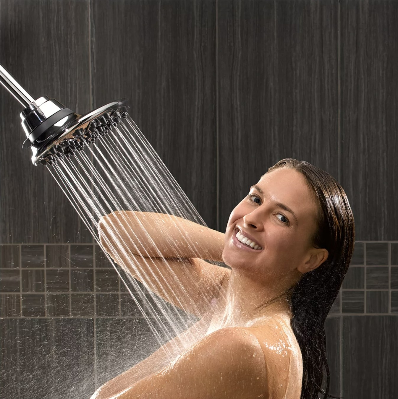 A model smiling under a showerhead spraying water