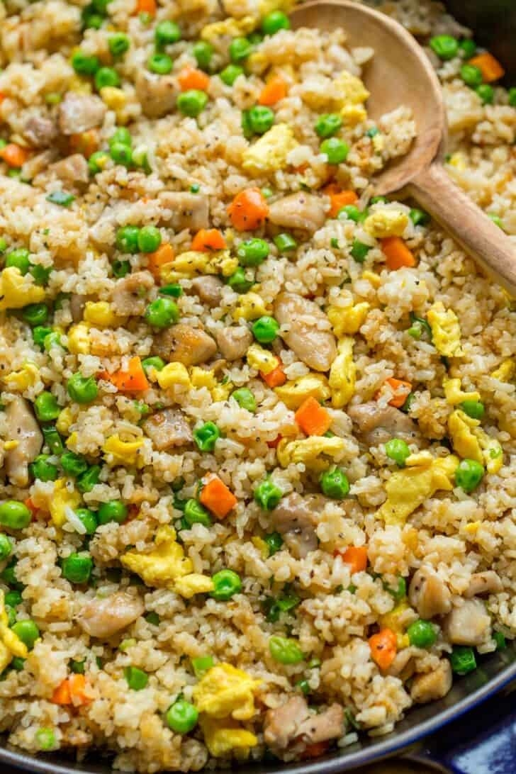 A big skillet of chicken and vegetable fried rice.