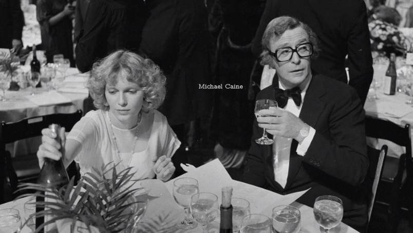 Michael Caine and Mia Farrow at a dinner table
