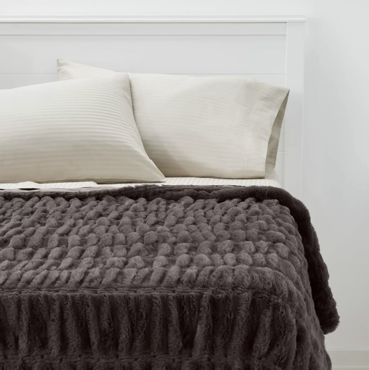 The brown faux fur throw blanket on a bed