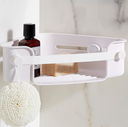 A close up of the triangular shelf suction-cupped into a shower stall