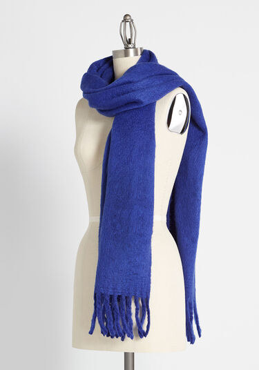 A bust form with the scarf wrapped around it in blue