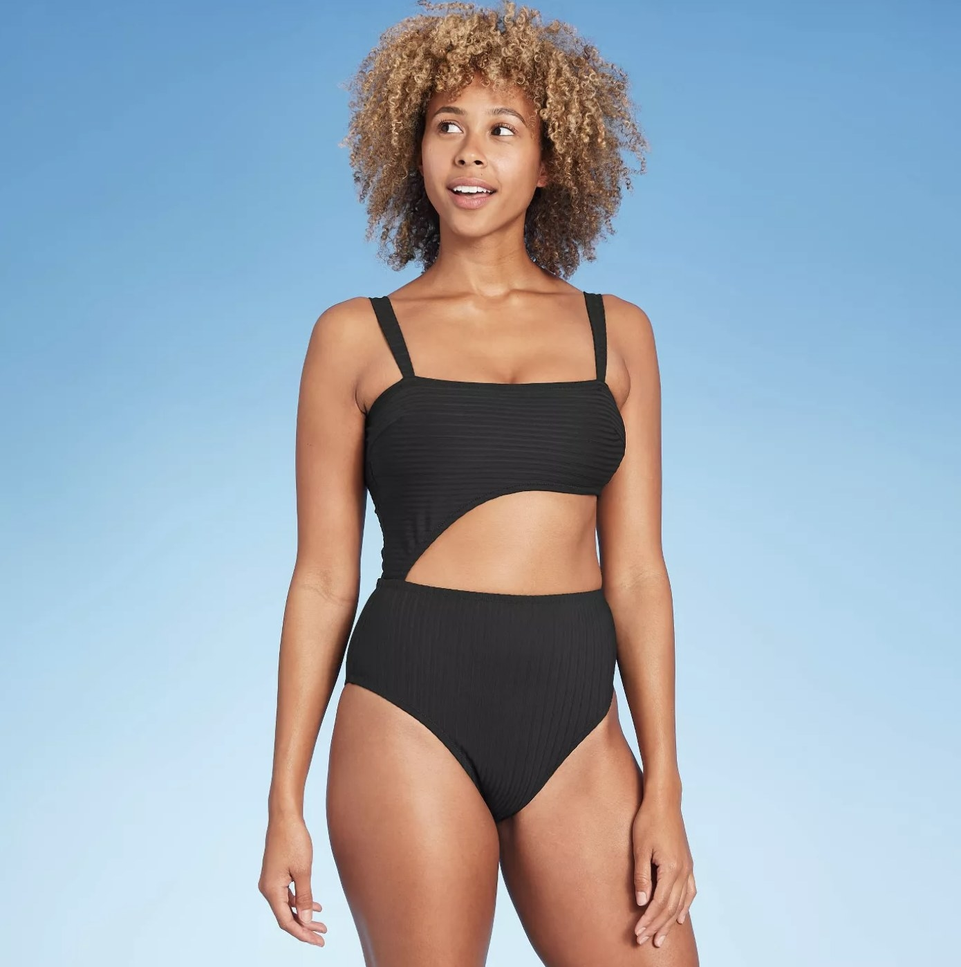 Model is wearing a black asymmetrical one-piece bathing suit