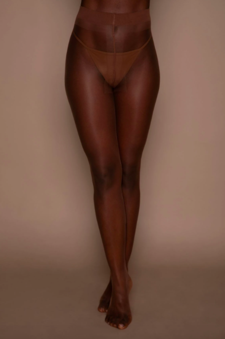 A model wearing the tights in cinnamon