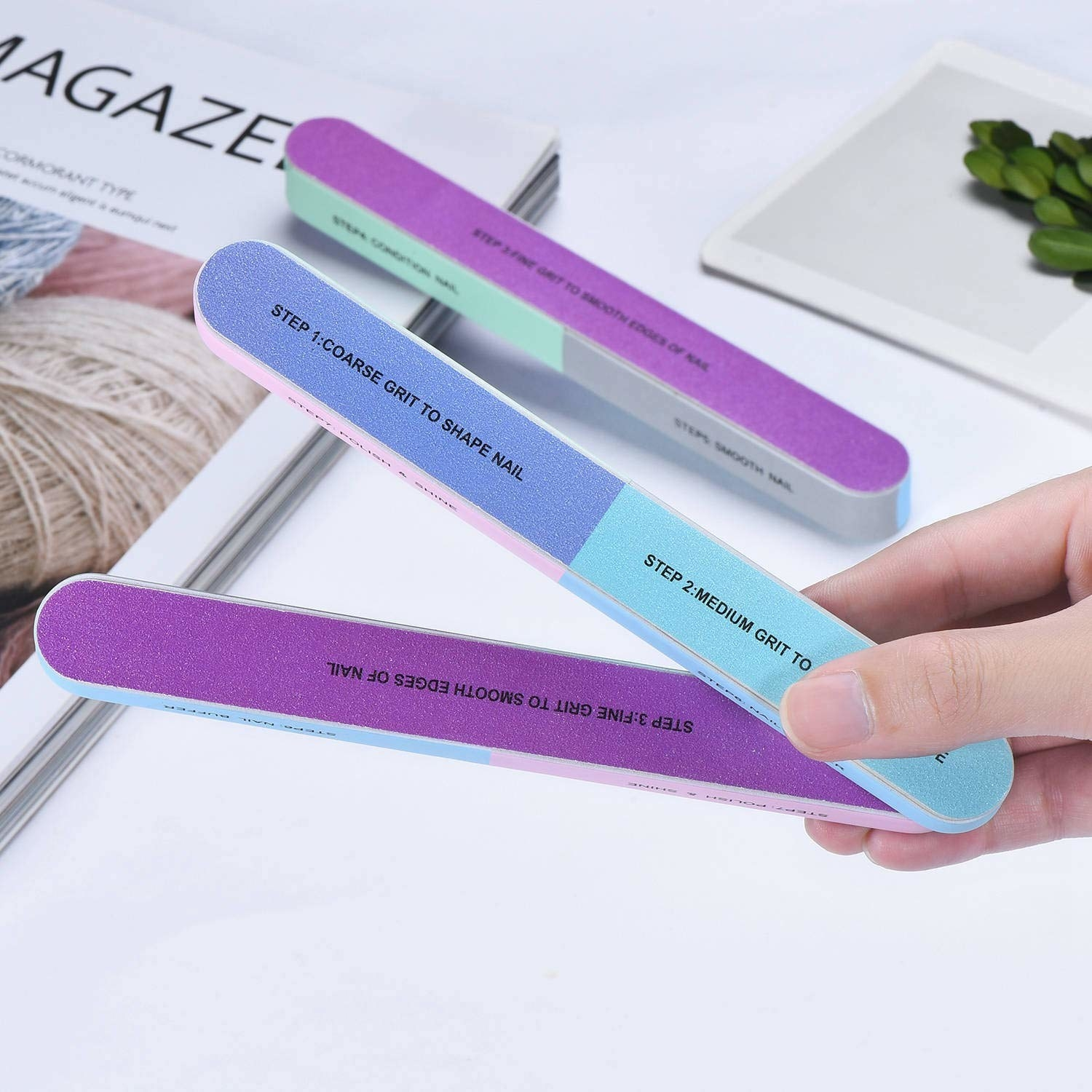 hand holds purple, blue, and pink multi-way nail buffer with step descriptions on each side