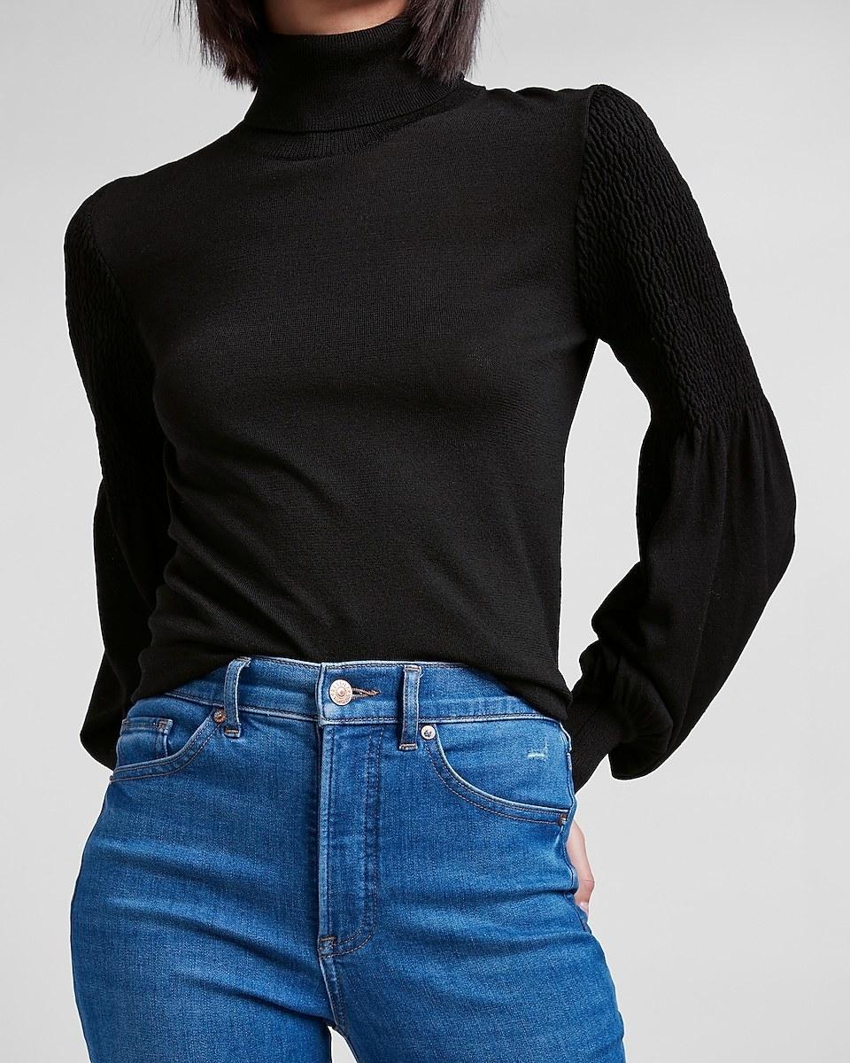 model wearing black turtleneck with smocked detail balloon sleeves