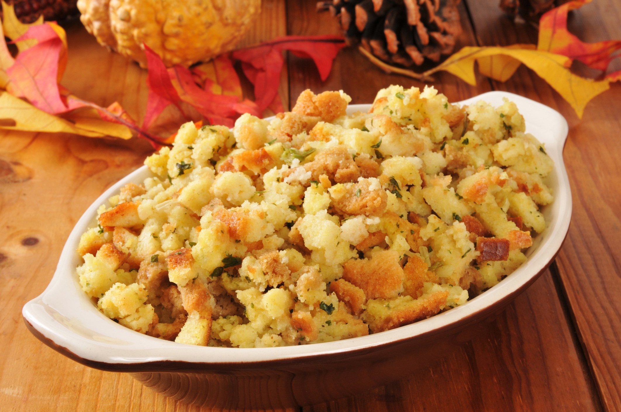 A small casserole dish of cornbread stuffing on a rustic wooden table.