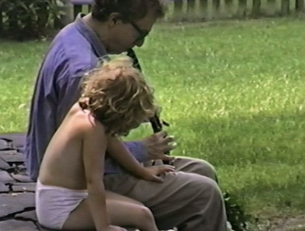 Archived footage of Woody Allen playing the flute next to a nearly-naked Dylan Farrow
