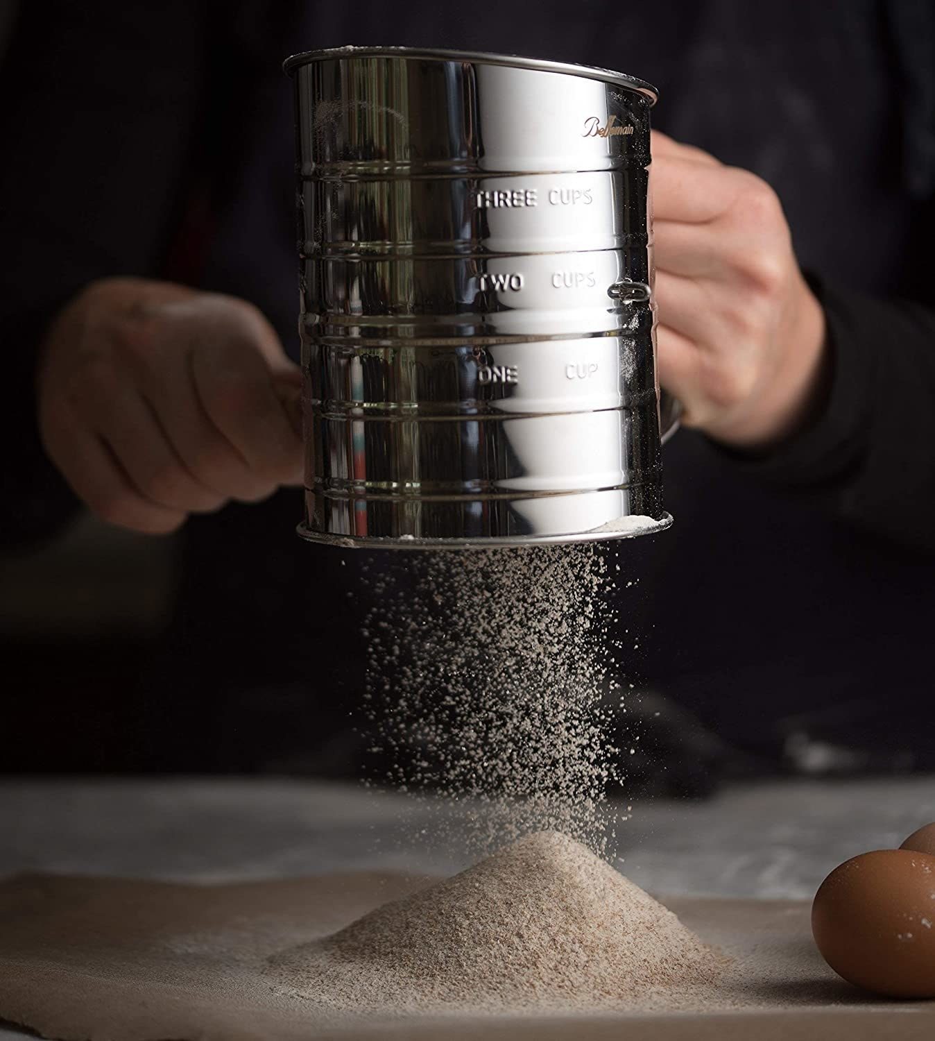 a model sifting flour through the stainless steel sifter