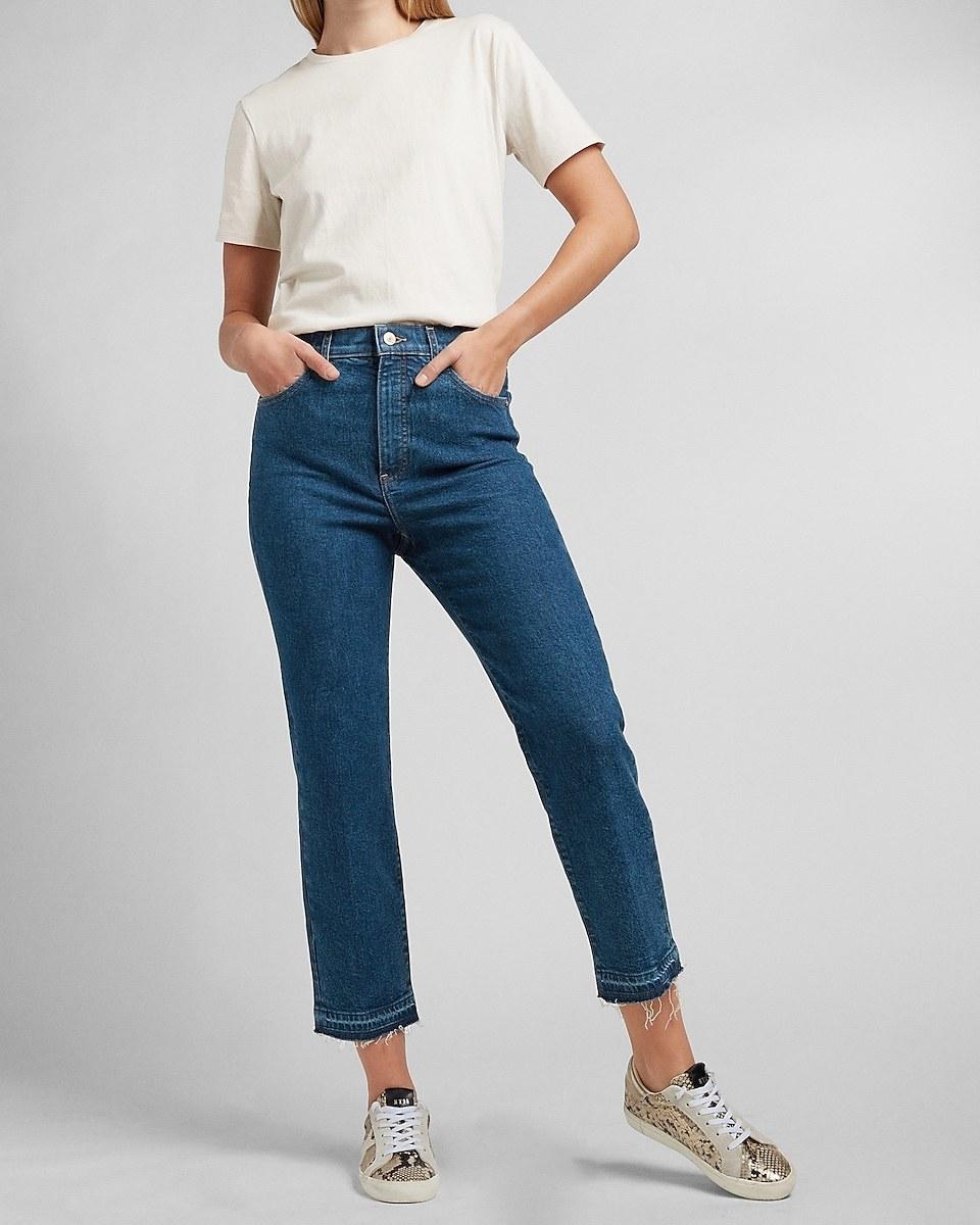 Model wearing the frayed hem medium wash jeans